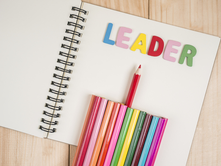 standout: Red pencil standout from colorful pencil on wood background, leadership business concept