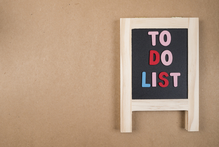 to do list: To do list on blackboard on brown paper background (Business Concept)