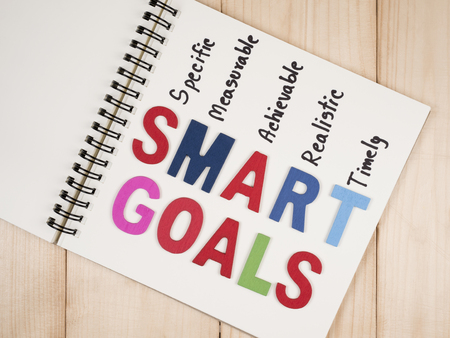 attainable: SMART Goals on blank notebook with wood background (Business Concept) Stock Photo