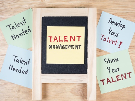 talent management: Handwriting Talent Management, Talent Needed, Talent Wanted, develop your talent, show your talent on colorful note paper and blackboard with wood background. Stock Photo