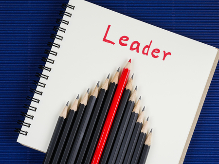standout: Red pencil standout from black pencil and handwriting word Leader on blank notebook with blue corrugate paper background, leadership business concept Stock Photo