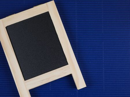 corrugate: Blank black board on blue corrugate paper background Stock Photo
