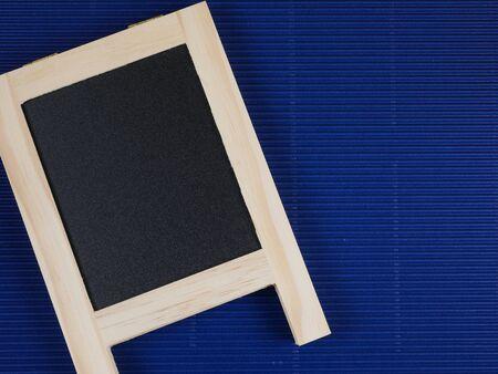 corrugate: Blank black board on blue corrugate paper background Stock Photo