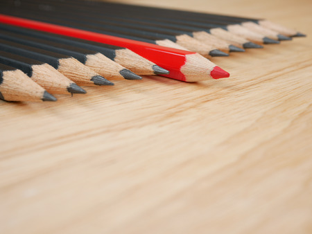 standout: Red pencil standout from black pencil on wood background, leadership business concept