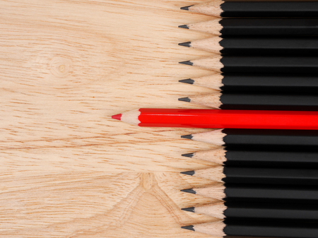 standout: Red pencil standout from black pencil with wood background, leadership business concept Stock Photo