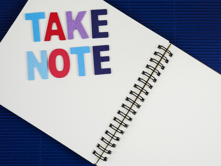 take a note: Word Take Note on notebook with blue corrugate paper background (Business concept) Stock Photo