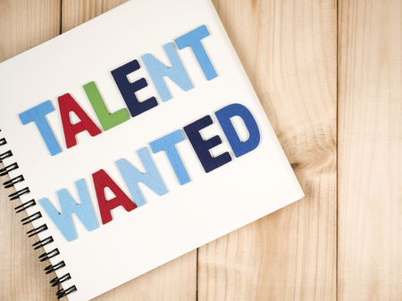 Font Talent Wanted on blank notebook with wood background
