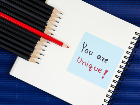 standout: Red pencil standout from black pencil and handwriting word You are unique on wood background, leadership business concept