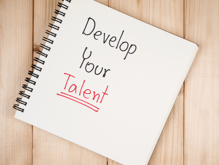 in need of space: Handwriting Develop Your Talent on blank notebook with wood background. (Business concept)
