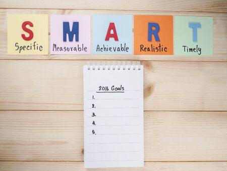 achievable: SMART Goals and 2016 Goals in notebook on wood background (Business Concept) Stock Photo
