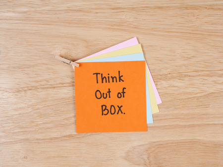 think out of the box: Handwriting word Think out of box on colorful note paper with wood background