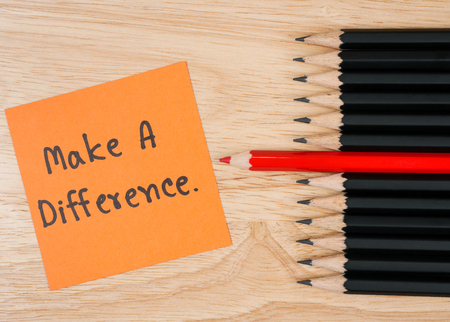 standout: Red pencil standout from black pencil and handwriting word Make a Difference on wood background, leadership business concept