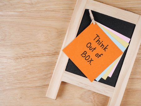 think out of the box: Handwriting word Think out of box on colorful note paper and blackboard with wood background
