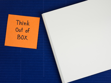 think out of the box: Handwriting word Think out of box on colorful note paper and notebook with blue paper background