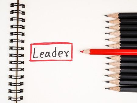 standout: Red pencil standout from black pencil and handwriting word Leader on wood background, leadership business concept