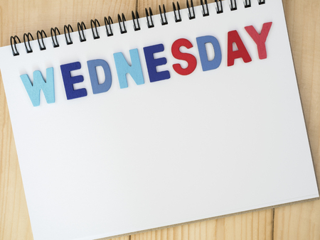 weekdays: Wednesday word spell by wooden letters on blank notebook with wood background (Weekdays word series) Stock Photo