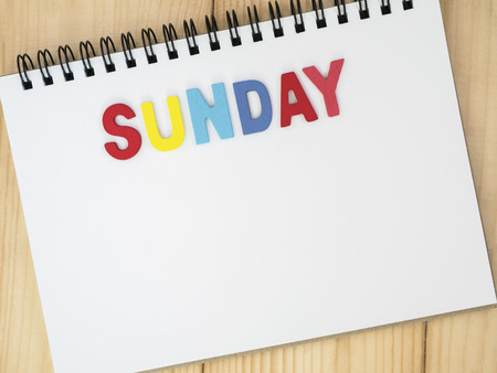 weekdays: Sunday word spell by wooden letters on blank notebook with wood background (Weekdays word series) Stock Photo