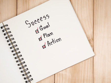 Handwriting word Success, Goal, Plan, Action on blank notebook with wood background (Business concept) Stock Photo