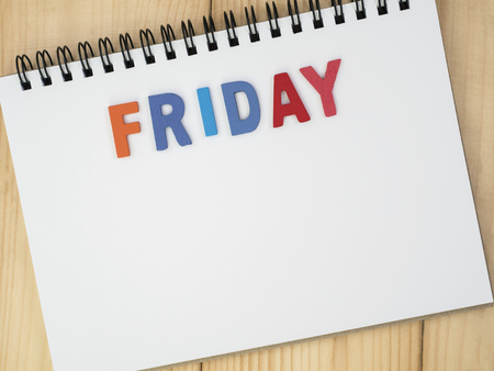 weekdays: Friday word spell by wooden letters on blank notebook with wood background (Weekdays word series) Stock Photo