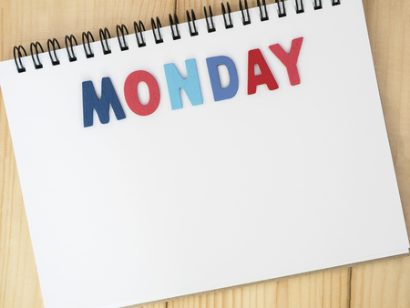 weekdays: Monday word spell by wooden letters on blank notebook with wood background (Weekdays word series)