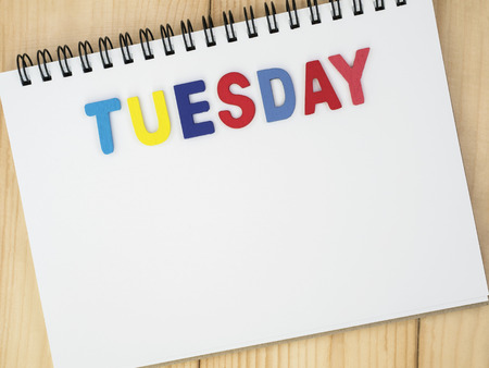 weekdays: Tuesday word spell by wooden letters on blank notebook with wood background (Weekdays word series) Stock Photo