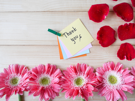 Red rose, pink flower and word Thank you on colorful note paper with wood background