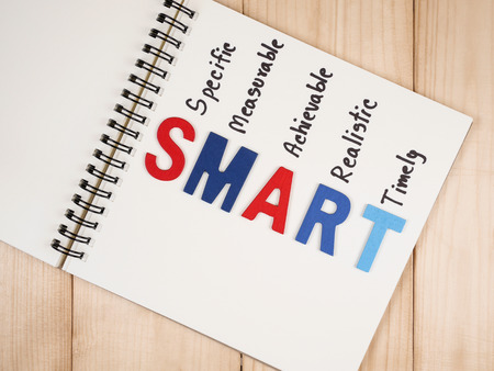 achievable: SMART Goals in notebook on wood background (Business Concept)