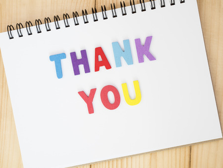 Font Thank you on blank notebook with wood background