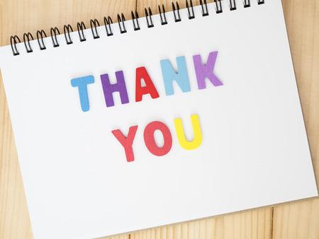 agradecimiento: Fuentes Gracias en el cuaderno en blanco con el fondo de madera