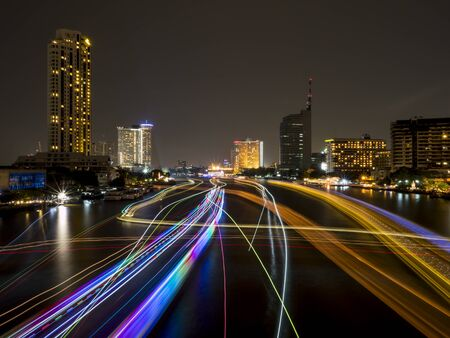 chao phraya river: The light trails from boat on the river and modern building, Night light at Chao Phraya River in Bangkok, Thailand