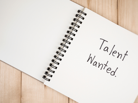 knack: Handwriting Talent Wanted on blank notebook with wood background (Business Concept)
