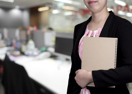 hand wear: One smart business woman wear black suit and hold brown notebook in left hand stand on office background (Business concept)