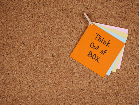 think out of the box: Handwriting word Think out of box on colorful note paper and notebook with cork board background