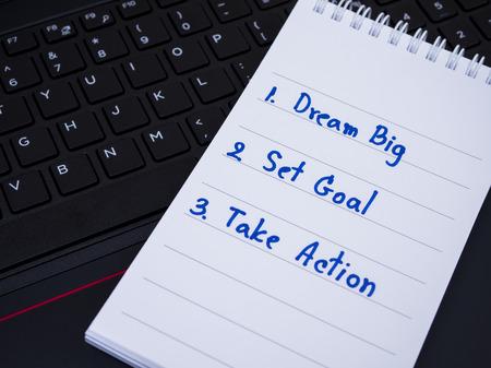 set goal: Dream Big, Set Goal , Take Action handwriting on notebook with black laptop keyboard  (Selective Focus)