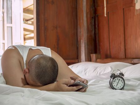 depress: Single man hold smart phone on his hand and bend down the head with feeling sad  unhappy  regret  depress on bed in the morning Stock Photo