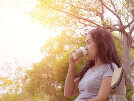 spiritless: Single women hold paper cup of coffee with feel lonely at the garden under sunlight in the morning with warm  soft color tone