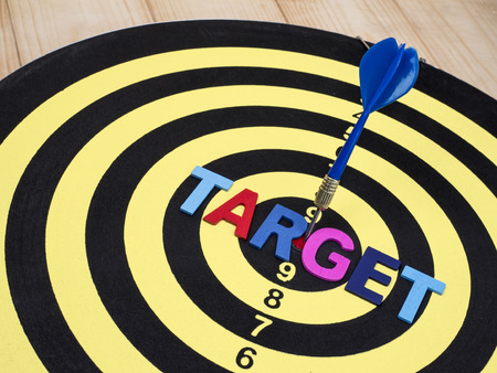 Word spell TARGET on dart board with blue arrow on isolated  white background with clipping path (Business Concept) Stock Photo