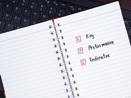 kpi: KPI (Key Performance Indicator) on white notebook with laptop keyboard (Business concept) Stock Photo