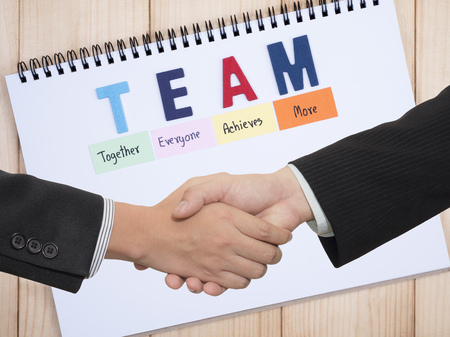 altogether: Handshake of two business mans waring black suit on word spell TEAM on white notebook (Teamwork concept) Stock Photo