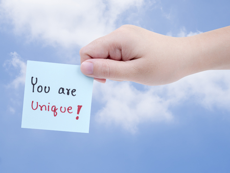 right path: Single woman hold handwriting word You are unique on note paper with right hand on blue sky background with clipping path
