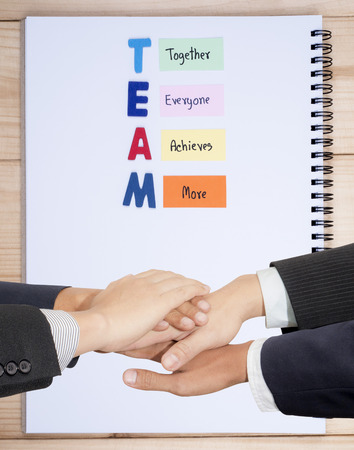 everyone: Business team join hand together Word spelling TEAM and handwriting together, everyone, achieve, more on notebook background