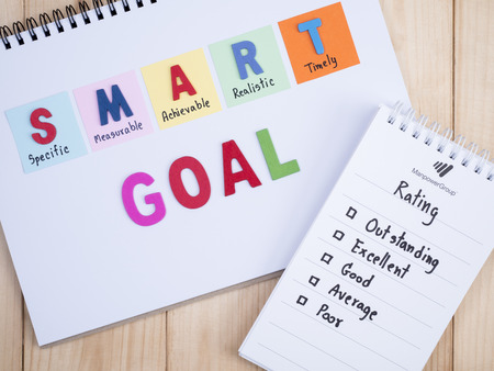 achievable: Handwriting Performance Rating and SMART Goal on notebook with wood background (Business Concept) Stock Photo