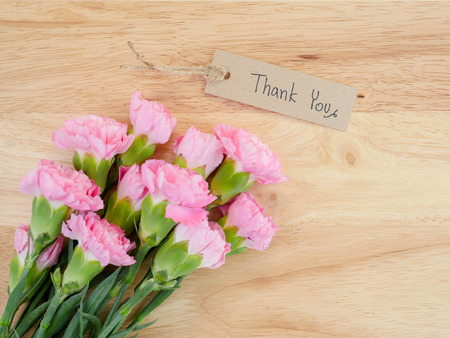gratefulness: Handwriting Thank you on brown label and bouquet of Carnation flower with wood background on top view