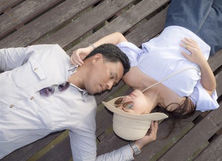 sprawl: Beautiful woman and handsome man of romantic couple are sprawl on wooden bridge