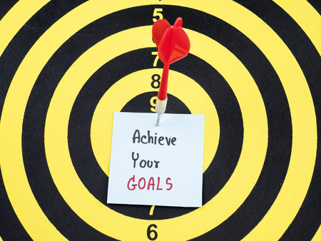 Handwriting Achieve your goals on notepaper with dart arrow and dart board. (Business concept) Stock Photo