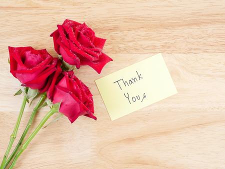 friendliness: Flor rosa roja y la escritura a mano en papel Gracias nota de color con fondo de madera Foto de archivo