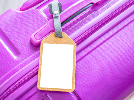 Close up of blank luggage tag on pink luggage bag