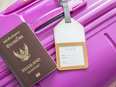 luggage tag: Closeup Thailand passport and luggage tag on pink suitcase