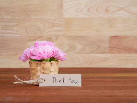 agradecimiento: Gracias escritura a mano en la etiqueta marrón y el ramo de la flor del clavel con fondo de madera