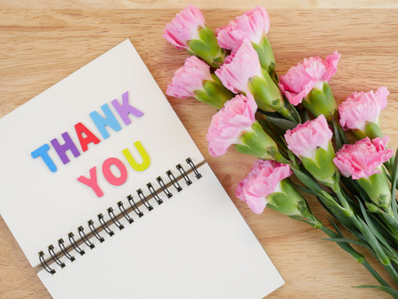 agradecimiento: Font Thank you on blank notebook and bouquet of Carnation flower with wood background on top view